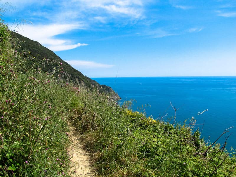 An empty Cinque Terre coastal trail with sea view and blue sky