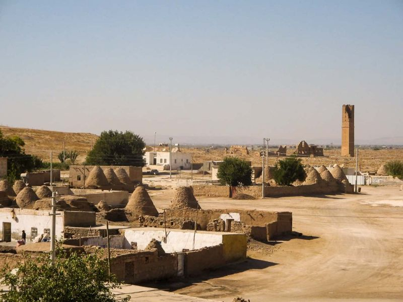 A view of Harran with the beehive houses, modern buildings, and astrological tower