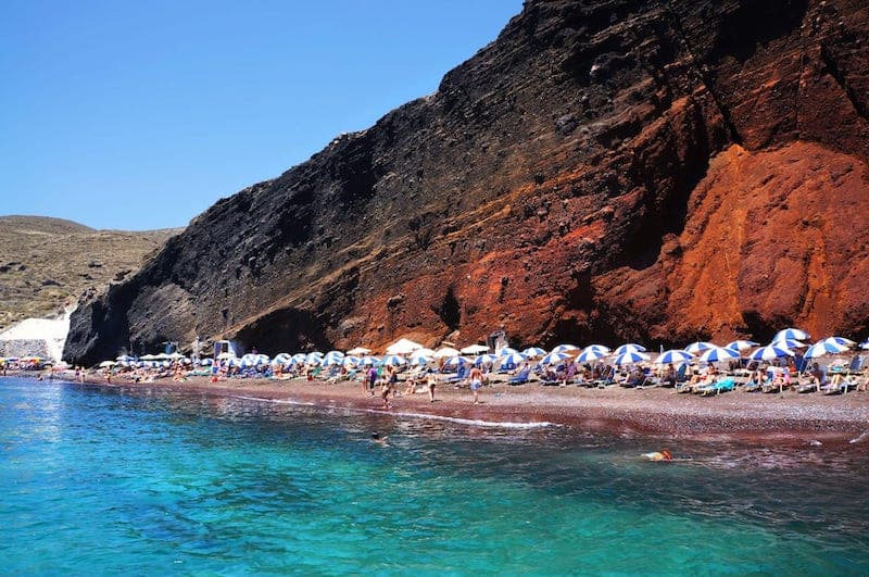 Santorini's Red Beach full of sunbathers, contrasting with turquoise sea