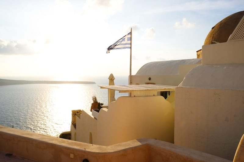A white building in Oia in the sunshine with a Greek flag flying