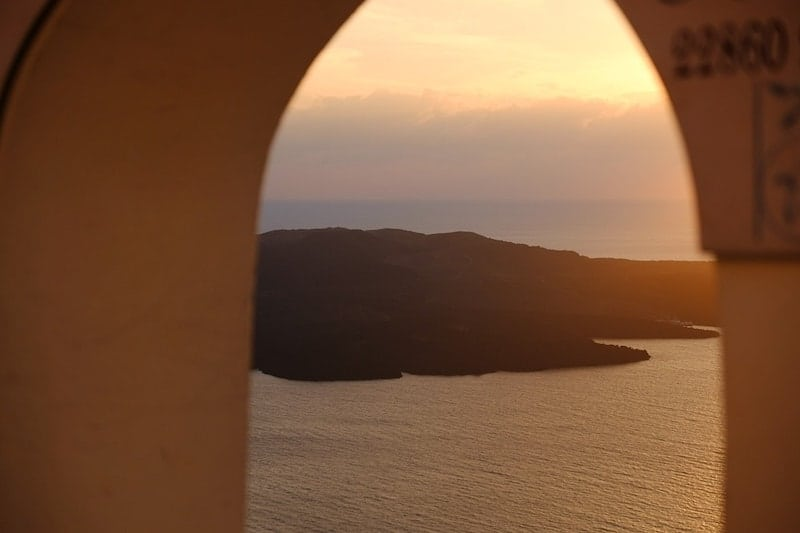 Sunset over the caldera through an archway in Fira