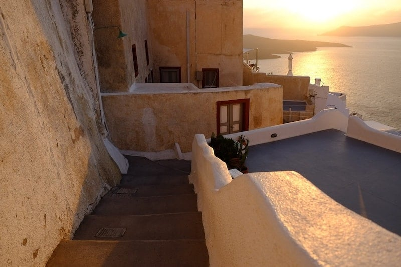 An empty alley in Fira glowing golden in the sun