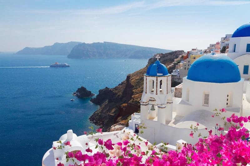 Bougainvillea and the blue-domed churches of Oia, Santorini