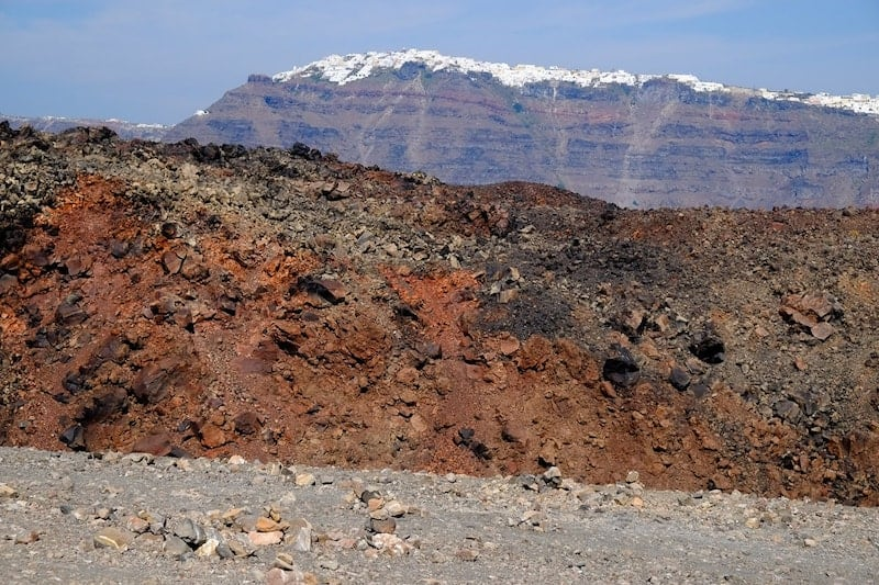 Red volcanic rock with Santorini caldera in background