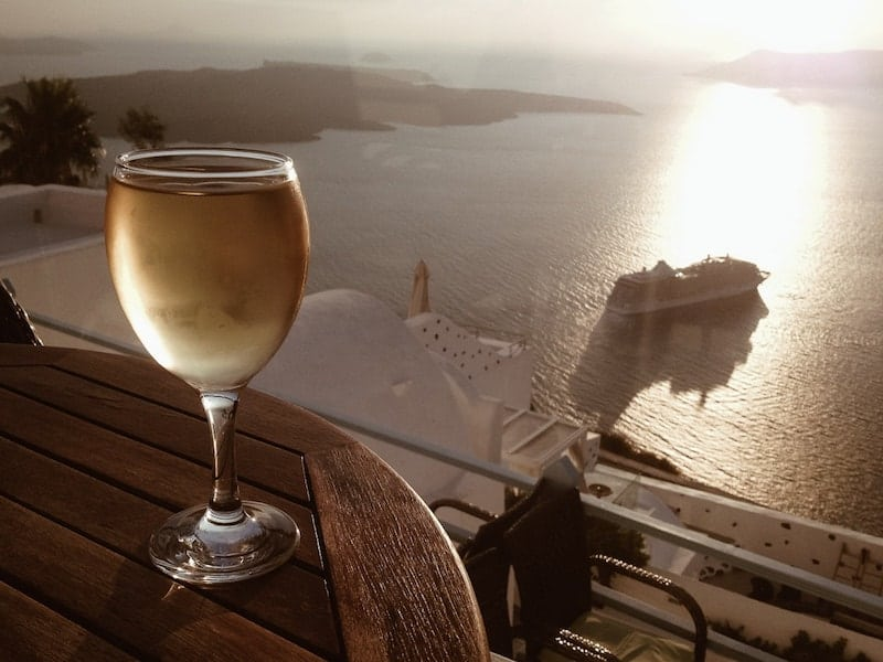 A glass of assyrtiko with a Santorini sunset backdrop
