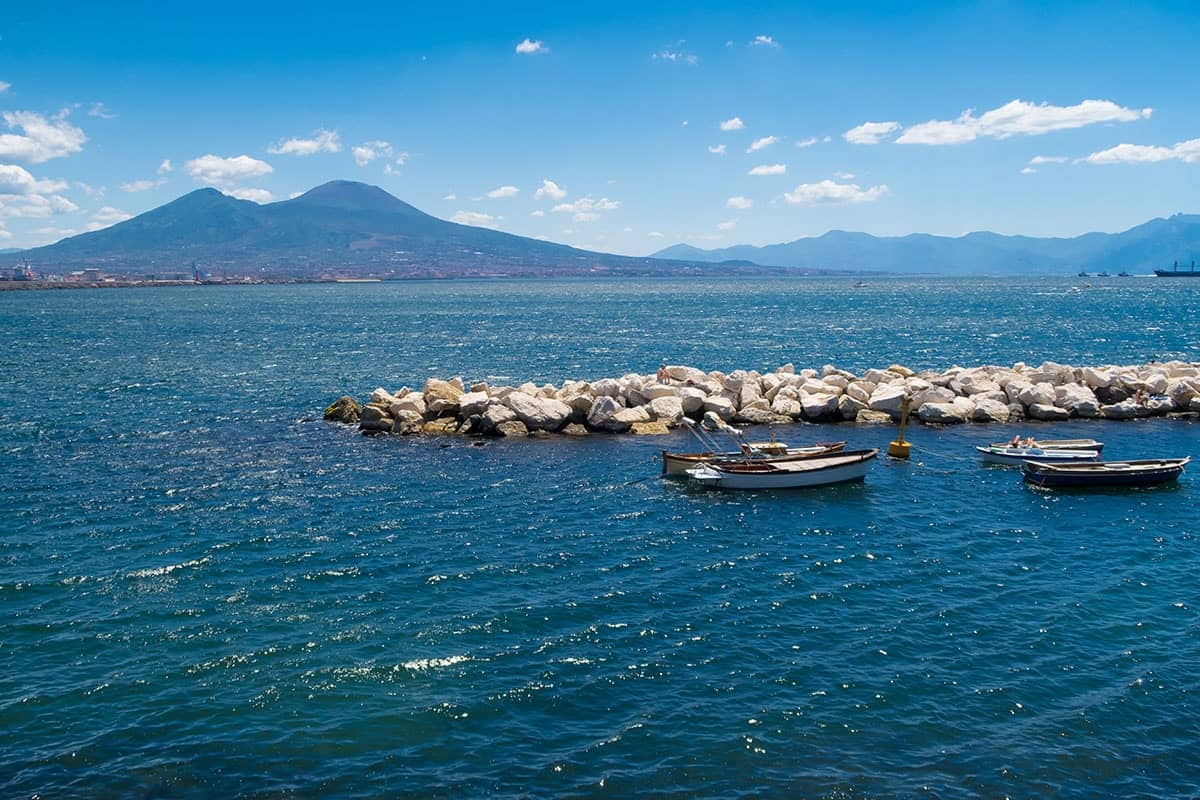 Small fishing boats in the sea with Vesuvius in the background