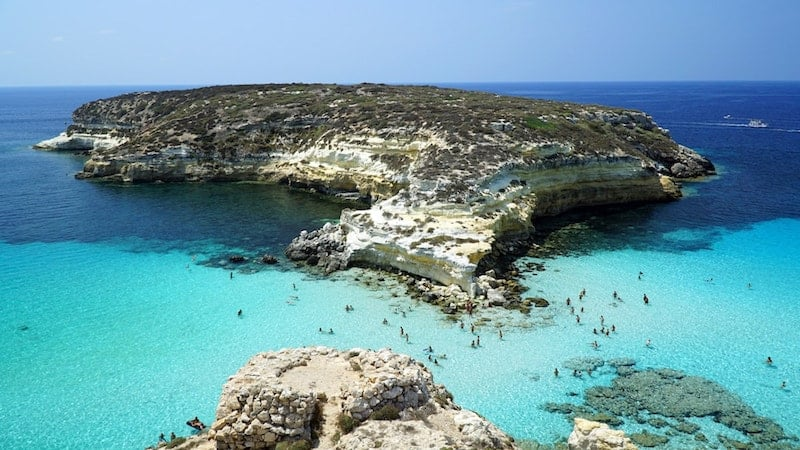 People swimming in the turquoise waters of Rabbit Beach, Lampedusa