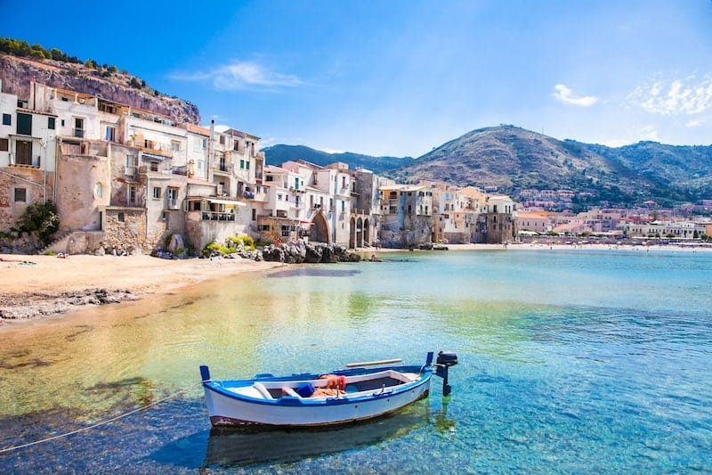 A fishing boat bobs in the water in front of Cefalu, Sicily