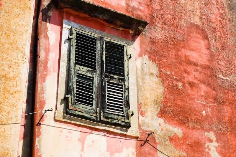 Old house with faded red paint and green window, Garitsa, Corfu Town