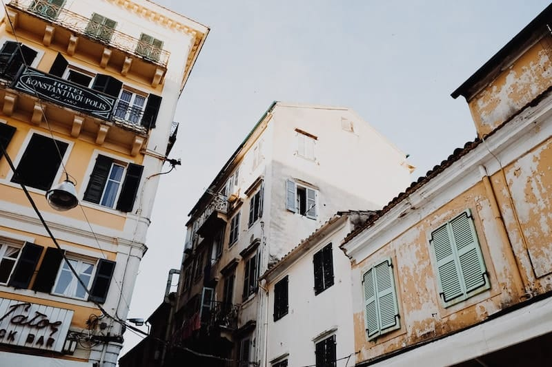 Looking up at tall buildings in Corfu's Old Quarter