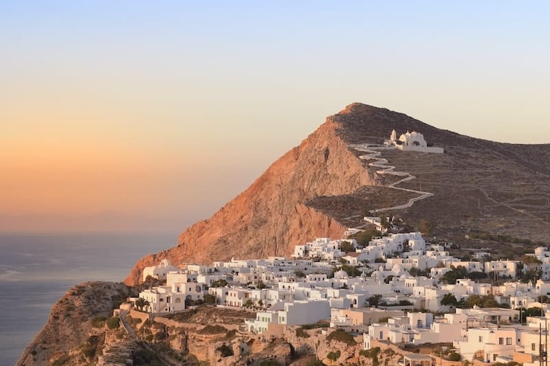 The clifftop whitewashed buildings of Folegandros at sunsest