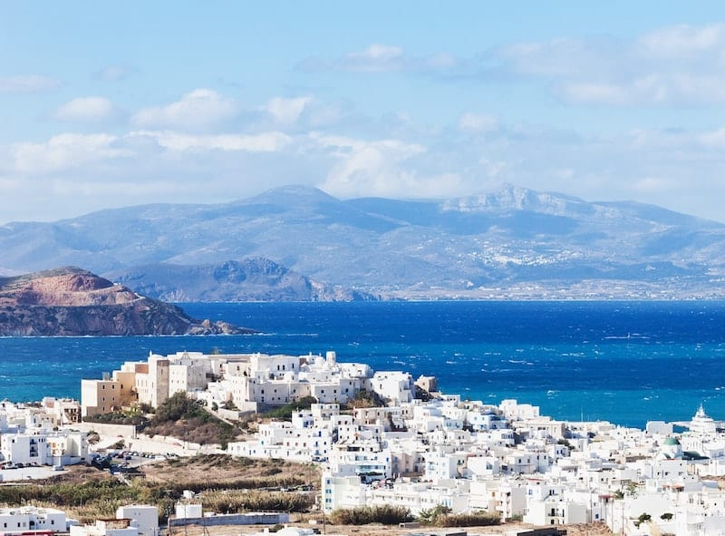White hilltop houses on Naxos with Paros across the channel in the background