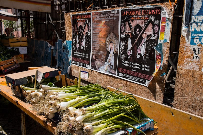 Spring onions for sale at Capo market in Palermo with flyers on the wall behind