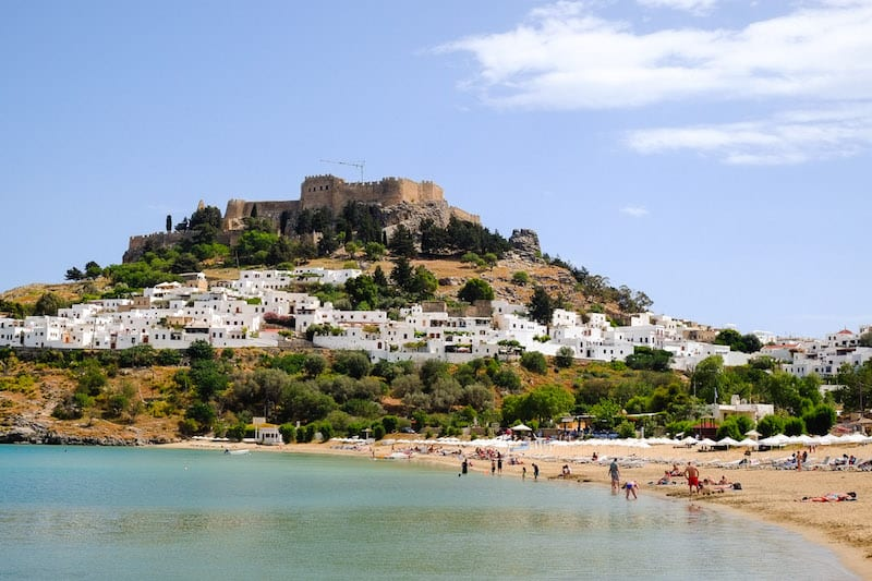 Sunworshippers on the beach in Lindos with the village and Acropolis in the background