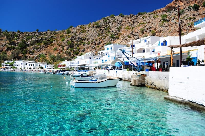 The white architecture of Loutro against turquoise water