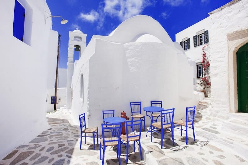 Blue chairs and tables outside a dazzling white church on Amorgos