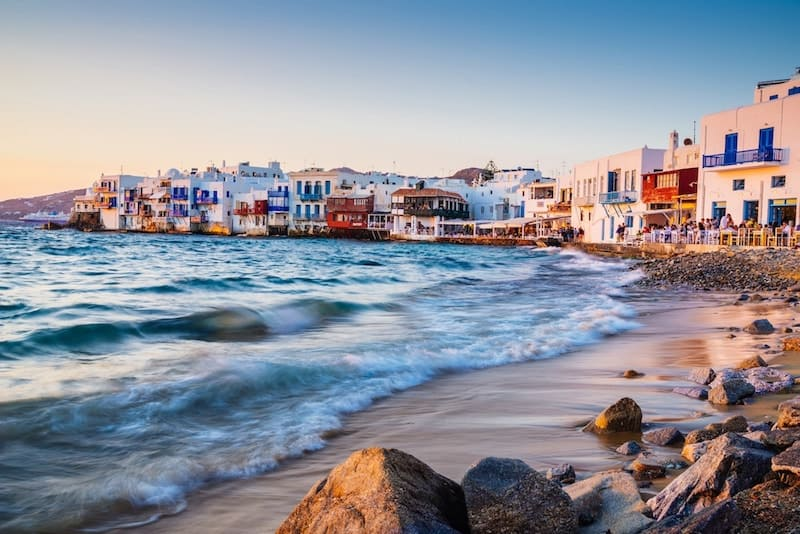 Waves break near the famous buildings of Little Venice in Mykonos at sunset