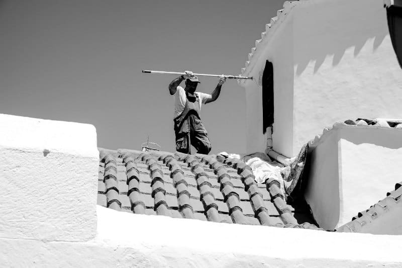 A local man applying white paint to a building exterior in Lindos