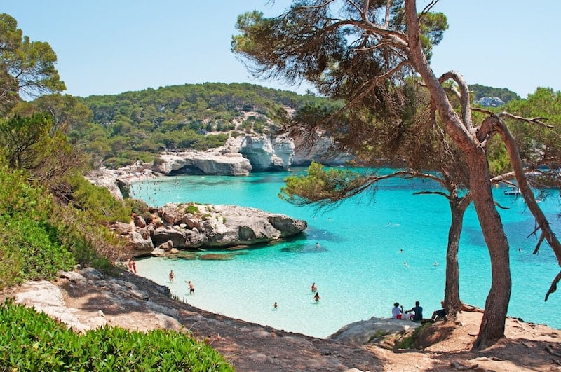 People bathing in the blue waters of Cala Mitjana on Menorca