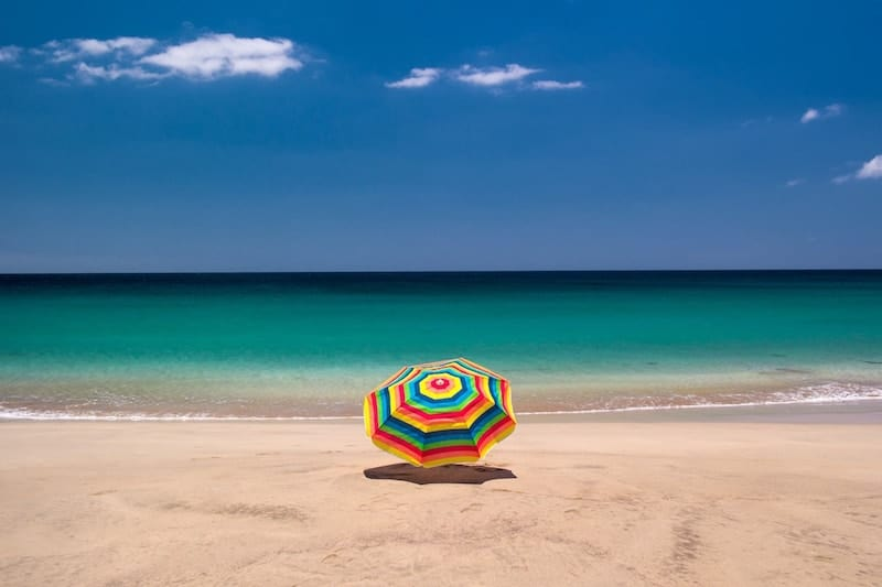 Sandy beach at Jandia, Fuerteventura, with colourful parasol