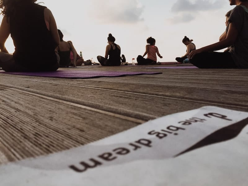 Sunset yoga on the pontoon with message 'the big dream'
