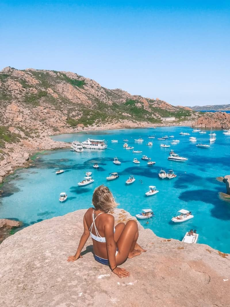 Greta looking out over boats anchored in a bay on the Costa Smeralda