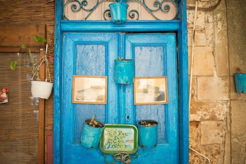 blue and yellow door in Crete with decorative hangings