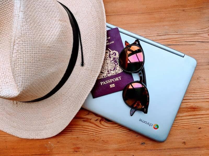 Chromebook with sunglasses, passport and sunhat