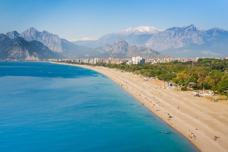 Long wide Konyaalti beach at Antalya with mountains in the background