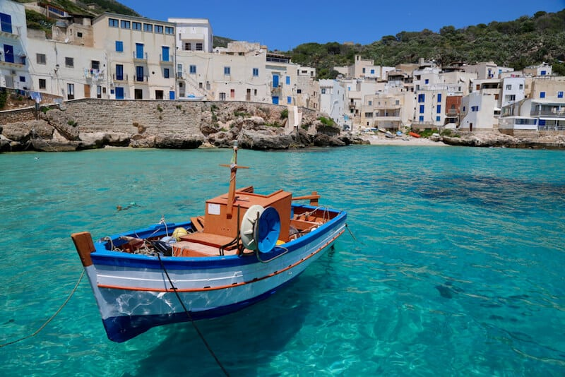 fishing boat bobs in Levanzo's turquoise waters