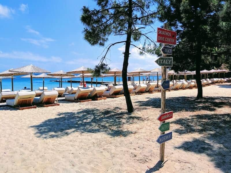 signs and sun loungers on Koukounaries beach