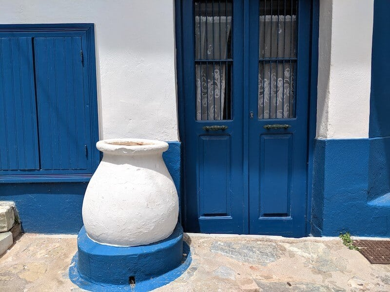blue and white building with large pot