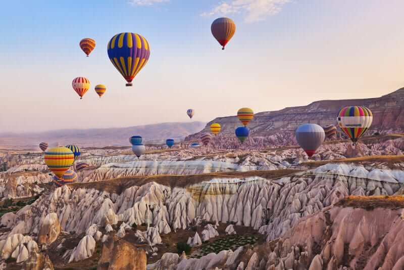 hot air balloons rising over the rock formations in Cappadocia