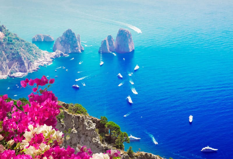 romantic view of Capri with rugged rocks and motorboats