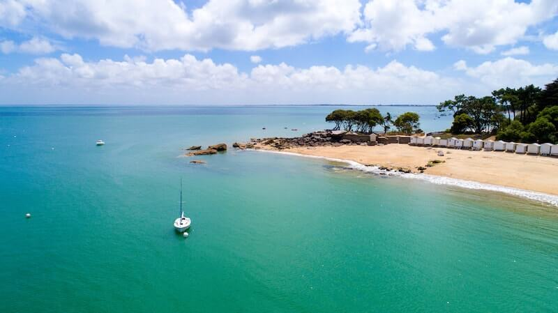 lone yacht anchored near Noirmoutier beach with trees and beach huts