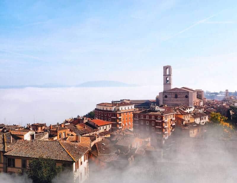 mist swirls around Perugia's historic buildings